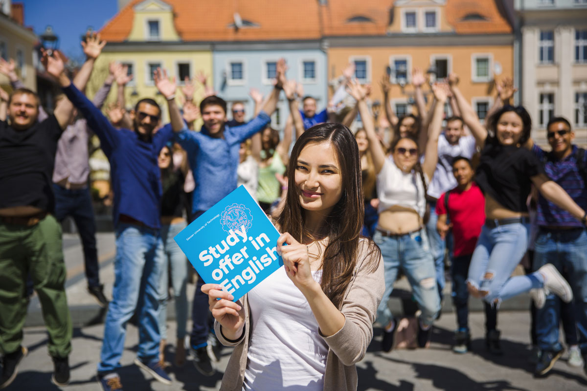 Stowarzyszenie Studentów BEST okazujący radość studenci i prezentująca księżkę studentka