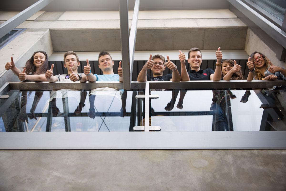 Studenci stojący na balkonie okazujący radość